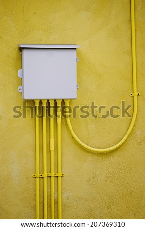 electrical box out door,on yellow wall - stock photo