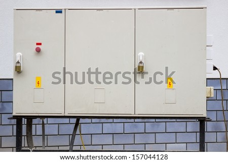 electrical cabinet with warning signs and padlocks at a street - stock photo