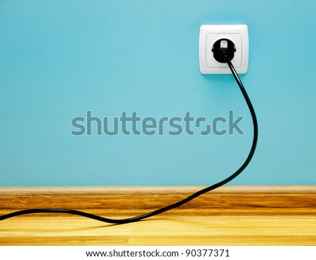 Electrical cable into the socket. Home shot.
