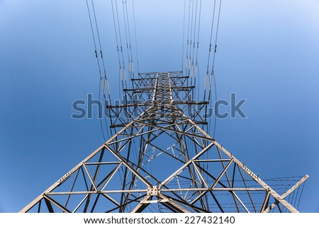 Electrical  Cables Tower Blue Electrical high voltage powerlines tower metal structure attached cables in blue sky - stock photo
