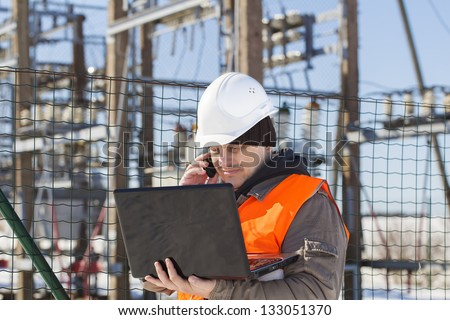 Electrical engineer with computer near the electricity substation - stock photo