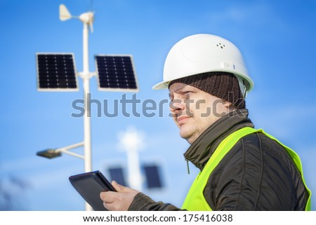 Electrical Engineer with tablet PC near street lighting with solar panels and wind generator  - stock photo