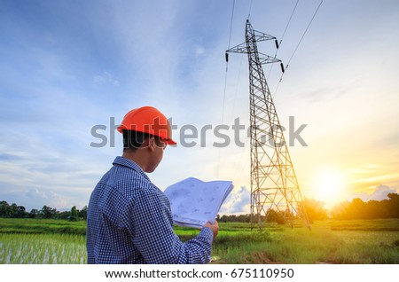 Electrical engineer working electrician holding blueprint stock electrician holding blueprint at high voltage power pylon against blue sky malvernweather Images