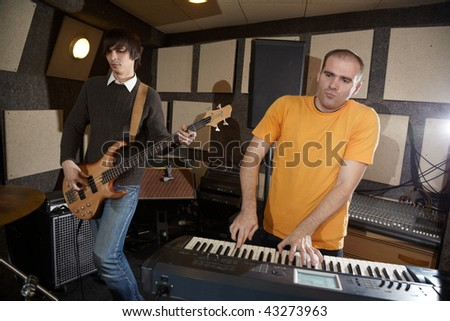 electrical guitar player and keyboarder working in studio - stock photo