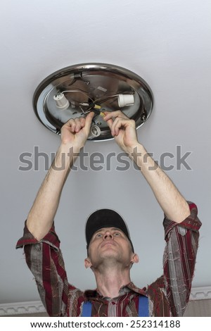 Electrical insulating contact on the ceiling lamp. - stock photo