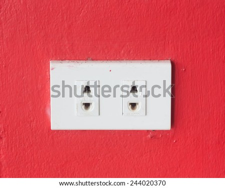 electrical outlet on red wall - stock photo