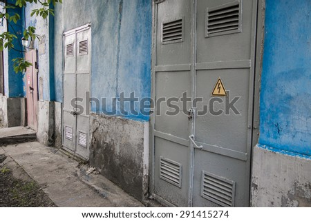 Electrical panel door with blue colored wall  - stock photo