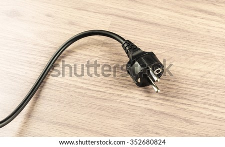 Electrical plug on a background of wooden floor in the room