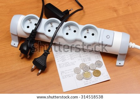 Electrical plugs with cords disconnected from electrical power strip, electricity bill with heap of coins, concept of energy saving. - stock photo