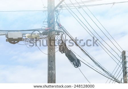 Electrical power pole with power cable and telephone cable against cloud sky - stock photo