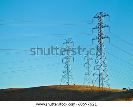 Electrical Powerlines on a Hill before a Blue Sky - stock photo