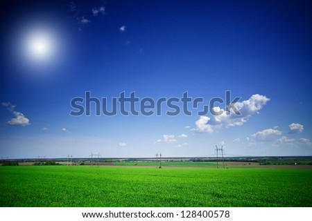 Electrical pylons ,green field of wheat and  blue sky. - stock photo