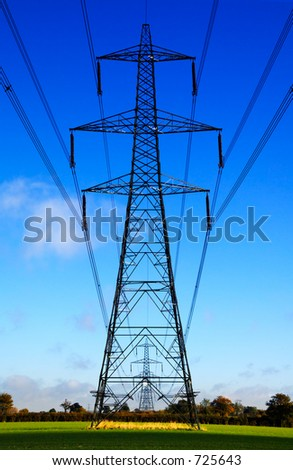Electrical sentries - electricity pylons in the English countryside - stock photo