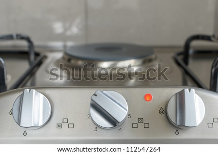 electrical stove knob in kitchen work top with operation light on - stock photo