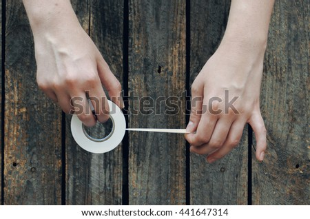 Electrical tape in hand on background wooden table