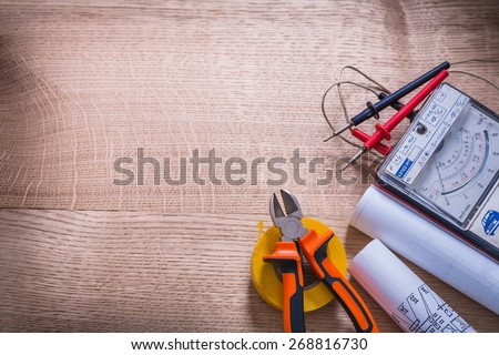 electrical tools multimeter tester nippers screwdriver roll insulating tape blueprint organized copyspace On Wooden Board  - stock photo