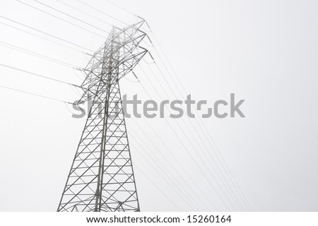 electrical tower of high voltage between light fog. Black and white