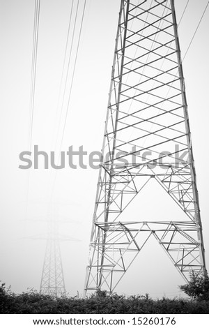 electrical towers of high voltage between light fog. Black and white