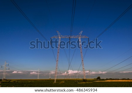 Electrical transmission line pylons along the corn field on the blue sky with clouds background
