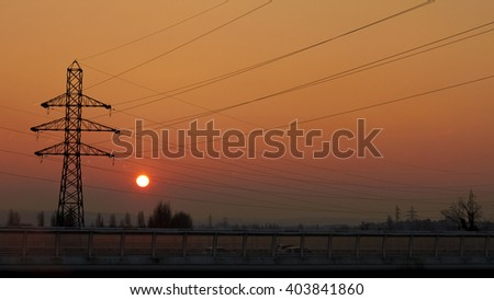 Electrical transmission tower, Energy transport, road transport. Against Sunset