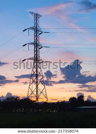 electrical transmission towers carrying high voltage  lines  at sunset