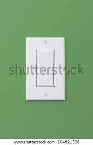 Electrical white rocker light switch on green wall - stock photo