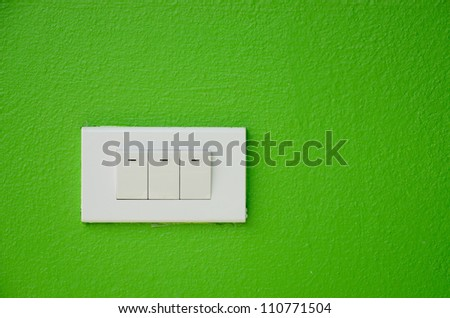 Electrical white rocker light switch on green wall. - stock photo