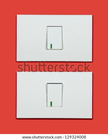 Electrical white rocker light switch on red wall. - stock photo