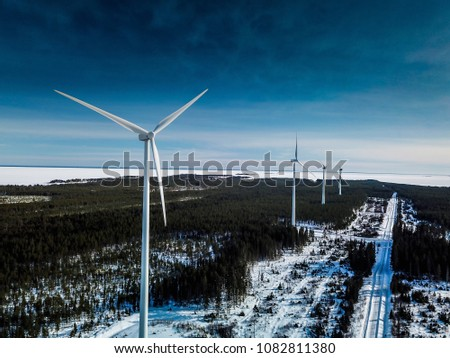 electrical windmills standing in raw along long road above pine tree forest sunny winter day sweden snow cold weather