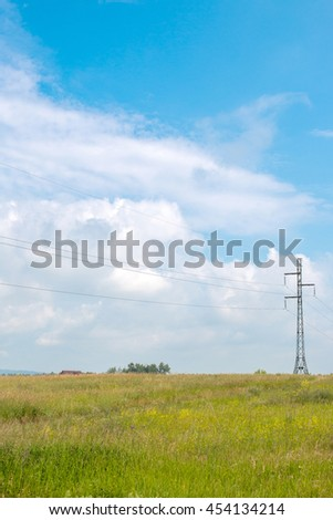 Electrical wires, pole, high-voltage line is through the field. Field overgrown with yellow flowers. Sunny summer day. the sky beautiful clouds.