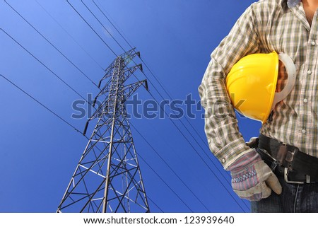 Electrician and high voltage power pylon against blue sky - stock photo