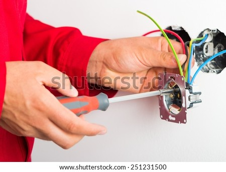 Electrician assembling new electrical outlet on wall. - stock photo