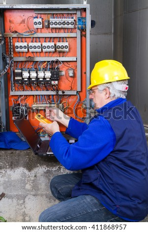 electrician at work with an electric panel