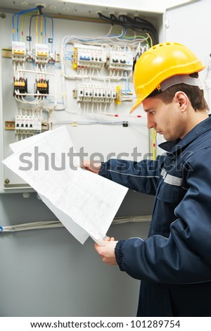 Electrician builder at work inspecting cabling connection of high voltage power electric line in industrial distribution fuseboard - stock photo