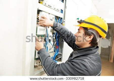 electrician builder at work installing energy saving meter into electric line distribution fuseboard - stock photo