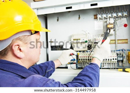 electrician builder at work with tester measuring high voltage and current of power electric line in electical distribution fuseboard. Focus on hands - stock photo