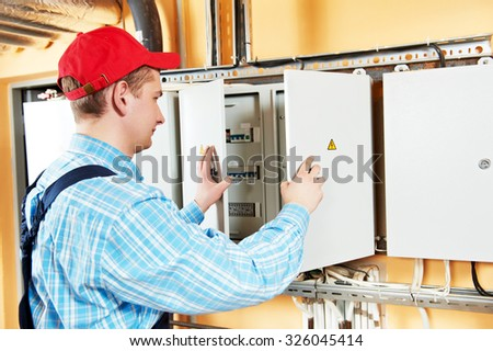 electrician builder engineer inspector checking data of equipment in fuse box - stock photo