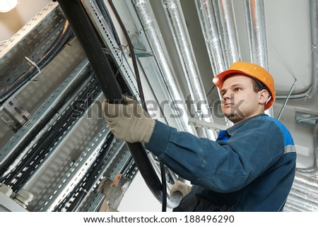 electrician builder engineer installing industrial cable into fuse box - stock photo