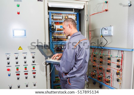 electrician builder engineer screwing and  testing equipment in fuse box (industrial machine) and repairing of electricity power station