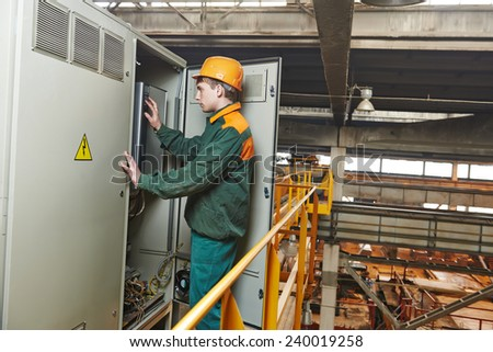 electrician builder engineer switching actuator equipment in distribution fuse box at factory - stock photo
