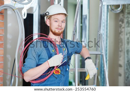 electrician builder engineer worker with cable wiring at indoor construction site - stock photo