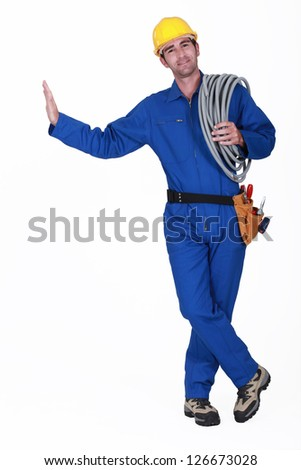 Electrician carrying spool of cable - stock photo