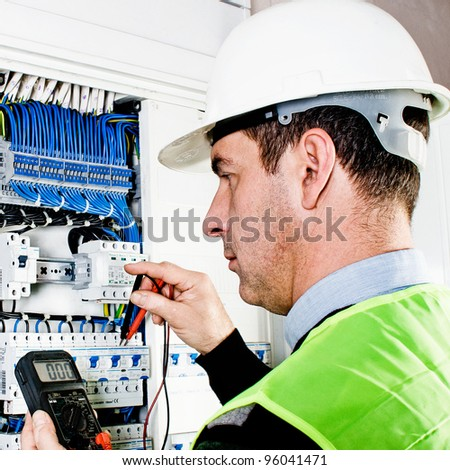 Electrician checking a fuse box - stock photo