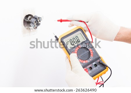 Electrician checking socket voltage with digital multimeter - stock photo