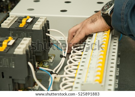 electrician connects wires to the machines