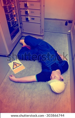electrician electrocuted - wounded man lying on the ground - stock photo