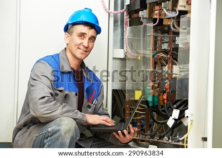 electrician engineer inspector with computer near the fuse box - stock photo