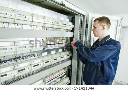 electrician engineer worker in front of fuseboard equipment in room - stock photo