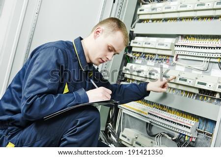 electrician engineer worker inspector  in front of fuseboard equipment in room - stock photo