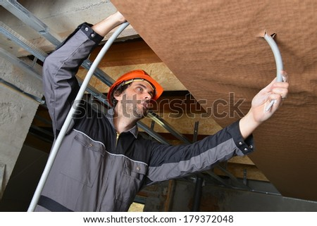 Electrician fitting a cable for ceiling light  - stock photo